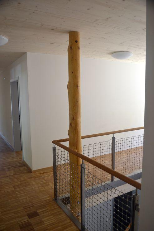 Baumstamm in Innenbereich mit statisch tragender Wirkung