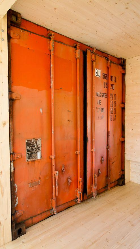 Starker Kontrast zwischen Stahlcontainer und Holzoberfläche